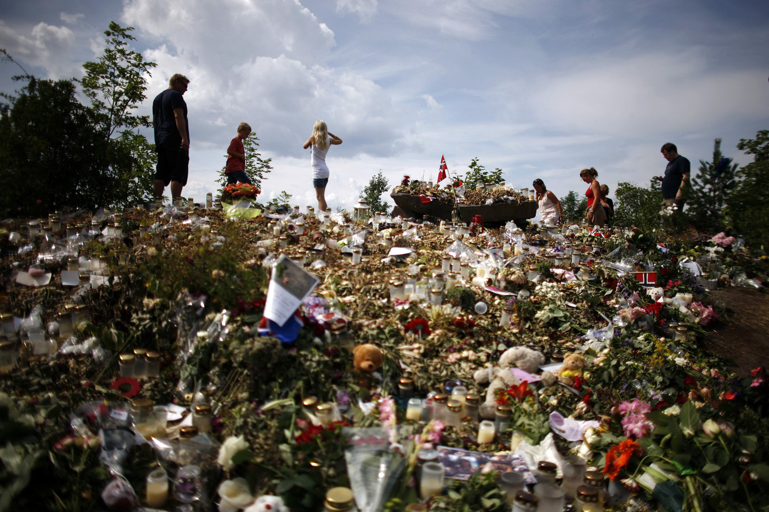 August 1, 2011. People stand on a memorial on the shore of Tyrifjorden lake overlooking Utoeya island in Norway, where anti-Islam extremist Anders Behring Breivik killed 68 people in a shooting rampage in July.