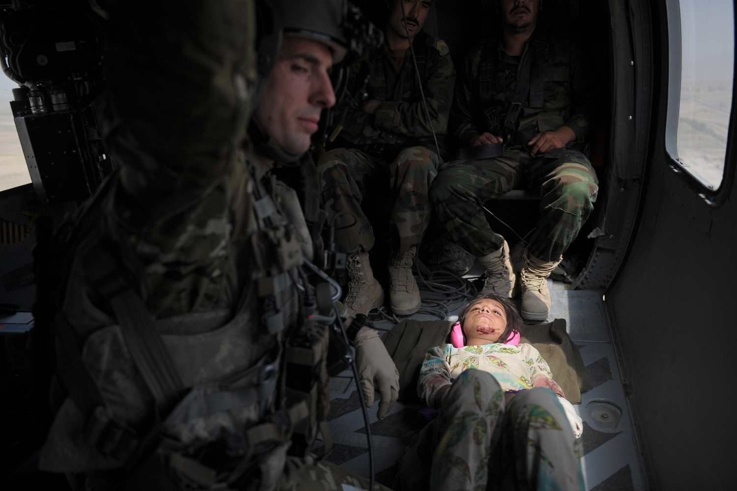 August 21, 2011. Semena (R), a ten-year old wounded Afghan girl, lies in a Medevac helicopter of U.S. Army 159th Brigade Task Force Thunder while being airlifted to a Kandahar hospital.