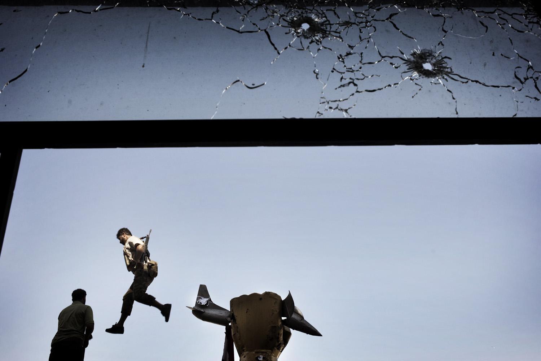 August 25, 2011. A rebel fighter leaps from a statue within Muammar Gaddafi's Bab al-Aziziya compound in Tripoli, Libya.