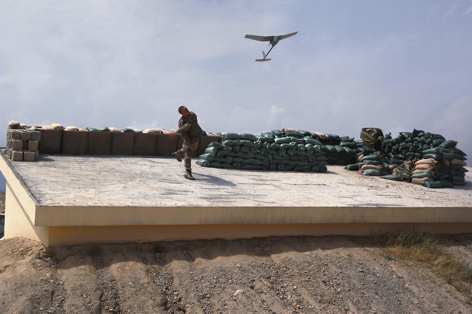 August 30, 2011. U.S. Army Sgt. Don Stolle launches a Raven surveillance drone into the air from the Afghan government district center in Achin, Afghanistan.