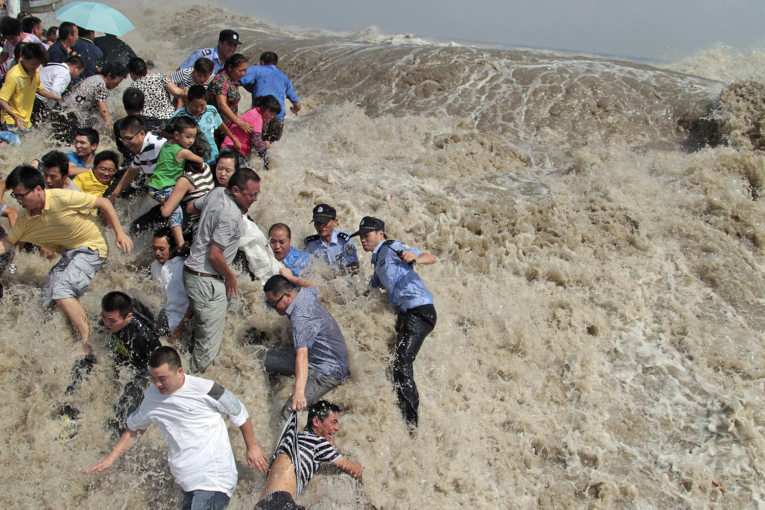 August 31, 2011. Policemen and residents run as waves from a tidal bore surge past a barrier on the banks of the Qiantang River in Haining, China.
