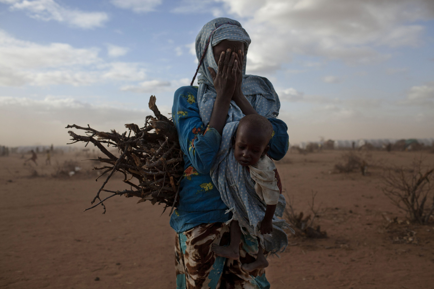 August 4, 2011. A refugee woman from Somalia carries sticks along with her baby in a new area of Dadaab refugee camp in Kenya.