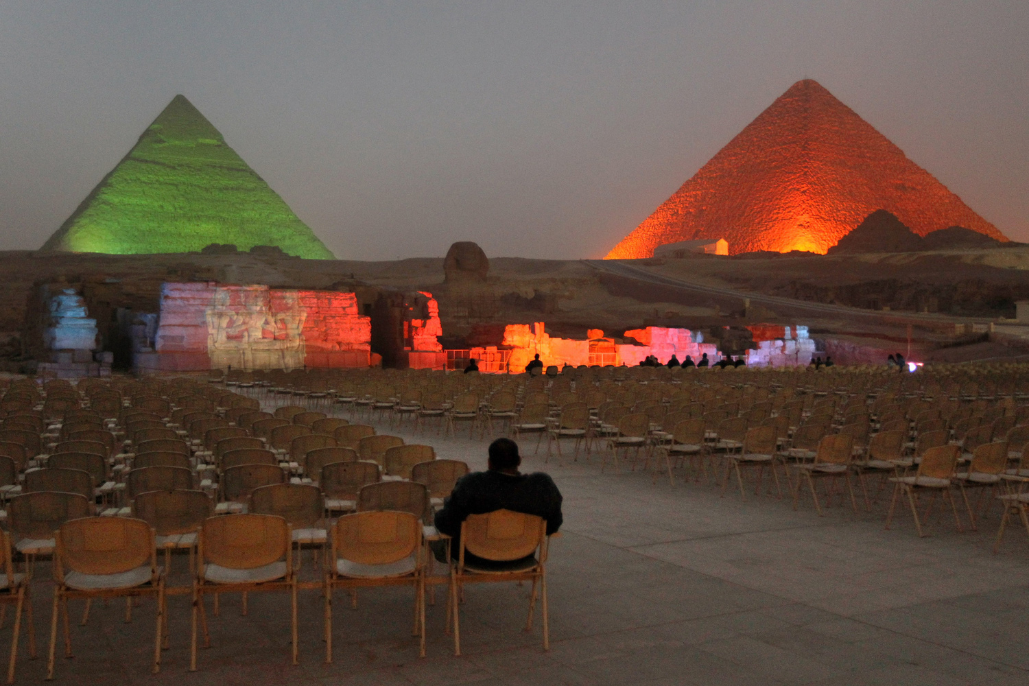 February 15, 2011. An Egyptian visitor watches a nearly empty light and sound show at the Giza pyramids on the outskirts of Cairo, Egypt.