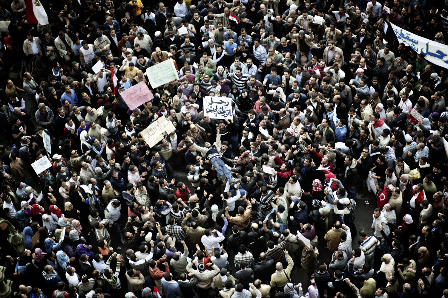 February 1, 2011. A crowd lifts a demonstrator during a protest march in Cairo's Tahrir Square.