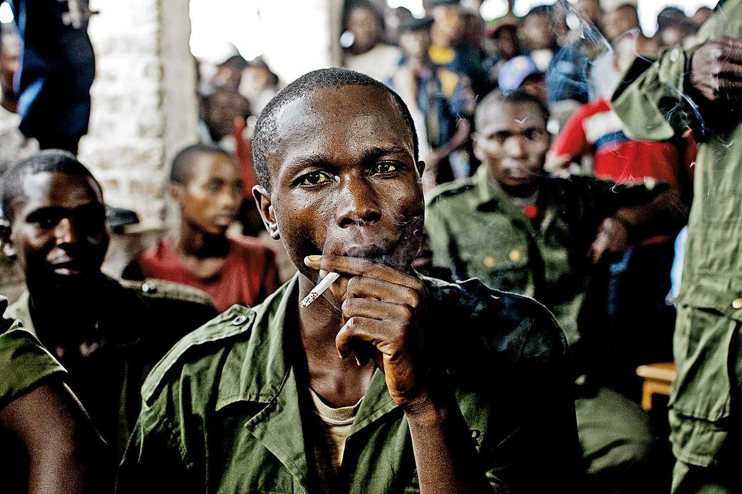 February 21, 2011. Sido Bizinungu, a close associate of Lt. Col. Mutuare Daniel Kibibi, smokes a cigarette after being convicted of crimes against humanity in the town of Baraka, Congo.