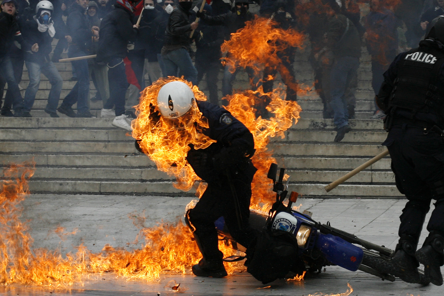 February 23, 2011. A policeman is seen in flames as he tries to escape after a petrol bomb was thrown at him during riots in front of the parliament in Athens, Greece.