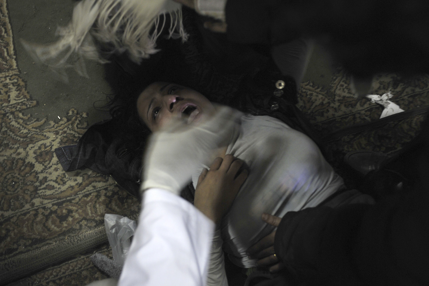 February 2, 2011. An injured Egyptian woman receives treatment at  an unidentified makeshift emergency treatment location as pro-Mubarak and anti-Mubarak protesters clash in Tahrir square, in Cairo, Egypt.