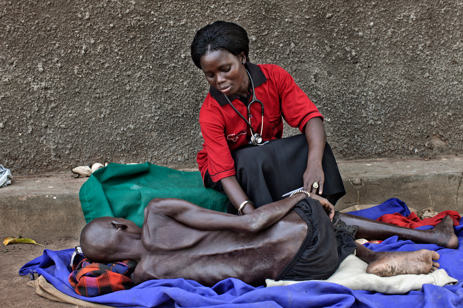 February 9, 2011. AMREF (African Medical and Research Foundation) officer Janet Mandera, 25-years-old, from Magui County, treats a woman that suffers from malnutrition at a center in Southern Sudan.