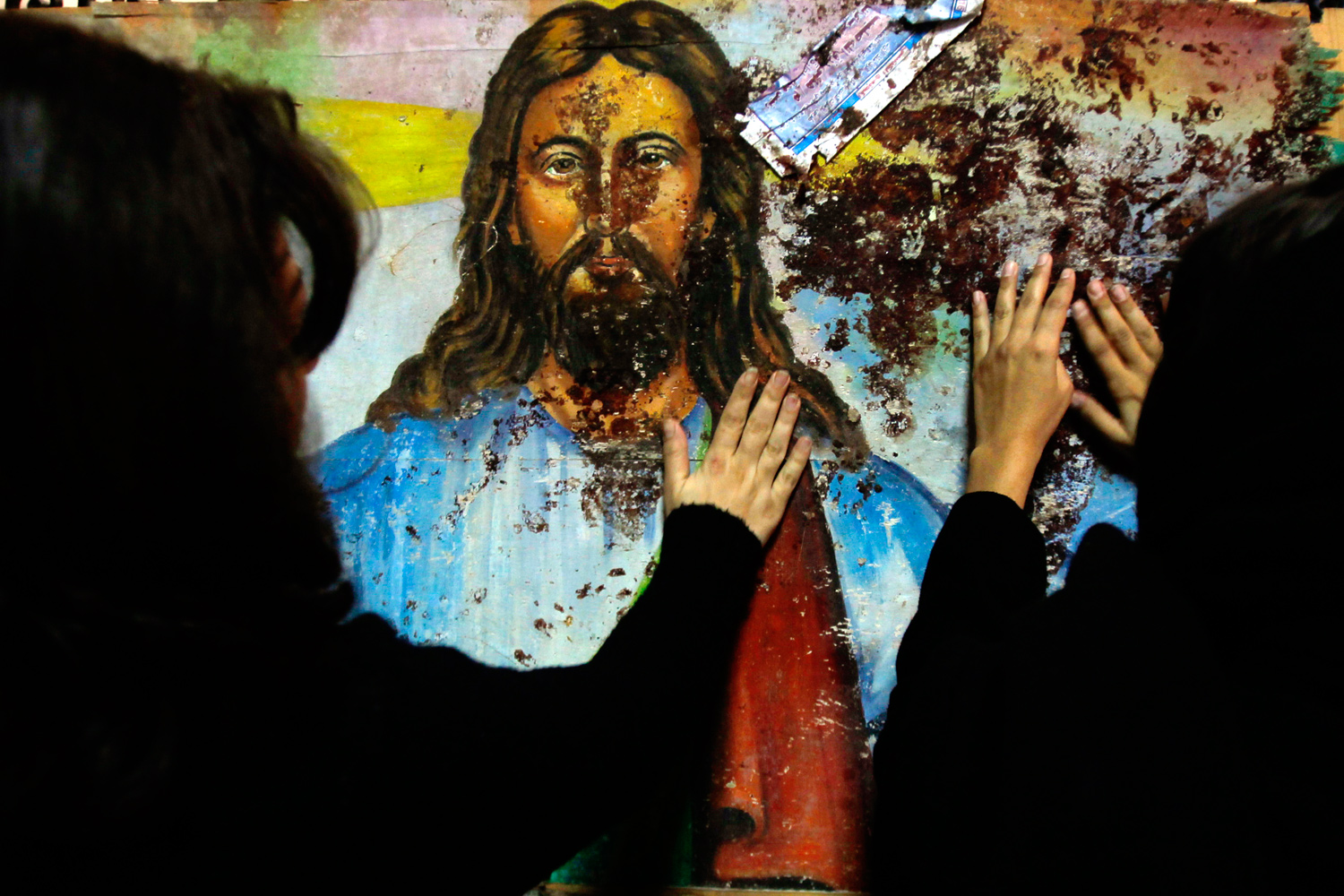 January 2, 2011. Egyptian Christians touch a blood-splattered image of Jesus Christ, inside the Coptic Orthodox church in Alexandria. A bomb killed at least 21 people outside the church early on New Year's Day and blood was splattered onto the image, which is located near the side gate of the church compound, during the bomb attack.