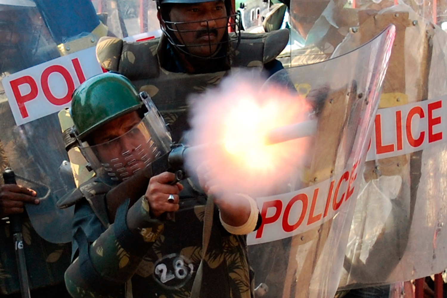 January 7, 2011. A policeman fires a teargas shell towards protesters during a demonstration in Hyderabad, India. Supporters of Telangana statehood say the interior region has been neglected in favor of Andhra Pradesh's dominant coastal districts.