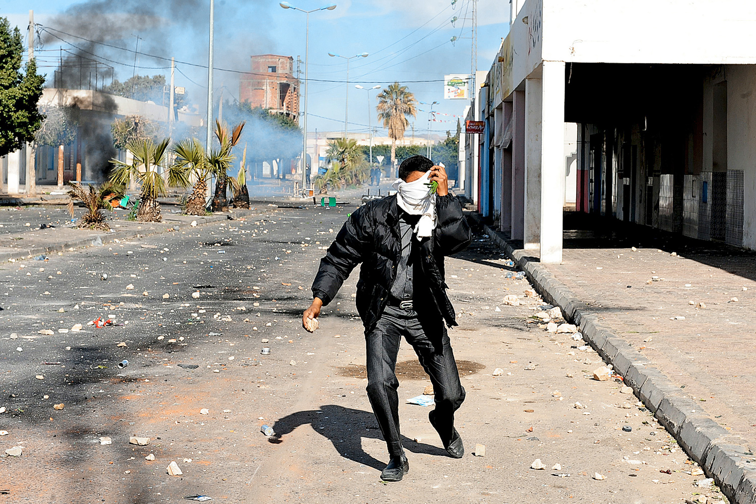 January 10, 2011. A Tunisian demonstrator covers his face as he holds a rock during clashes with security forces in Regueb.
