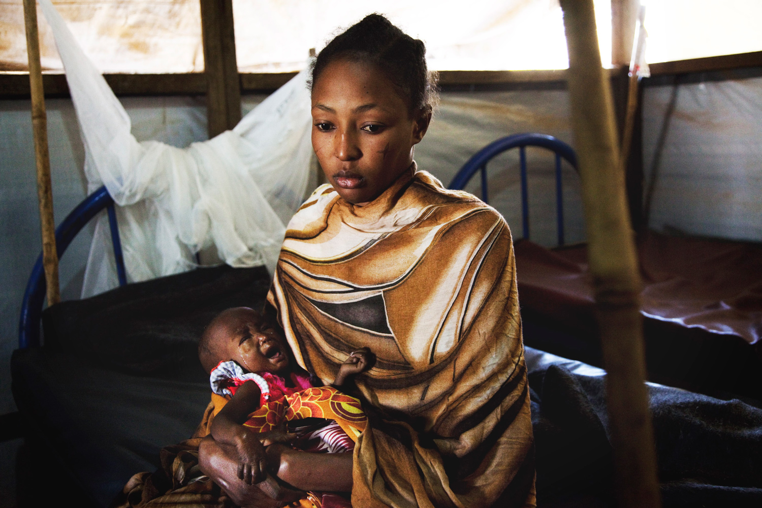 January 11, 2011. Eclas Ahomed, a 20-year-old internal refugee from Northern Sudan cares for her malnourished baby in the intensive care ward at an Aweil hospital.
