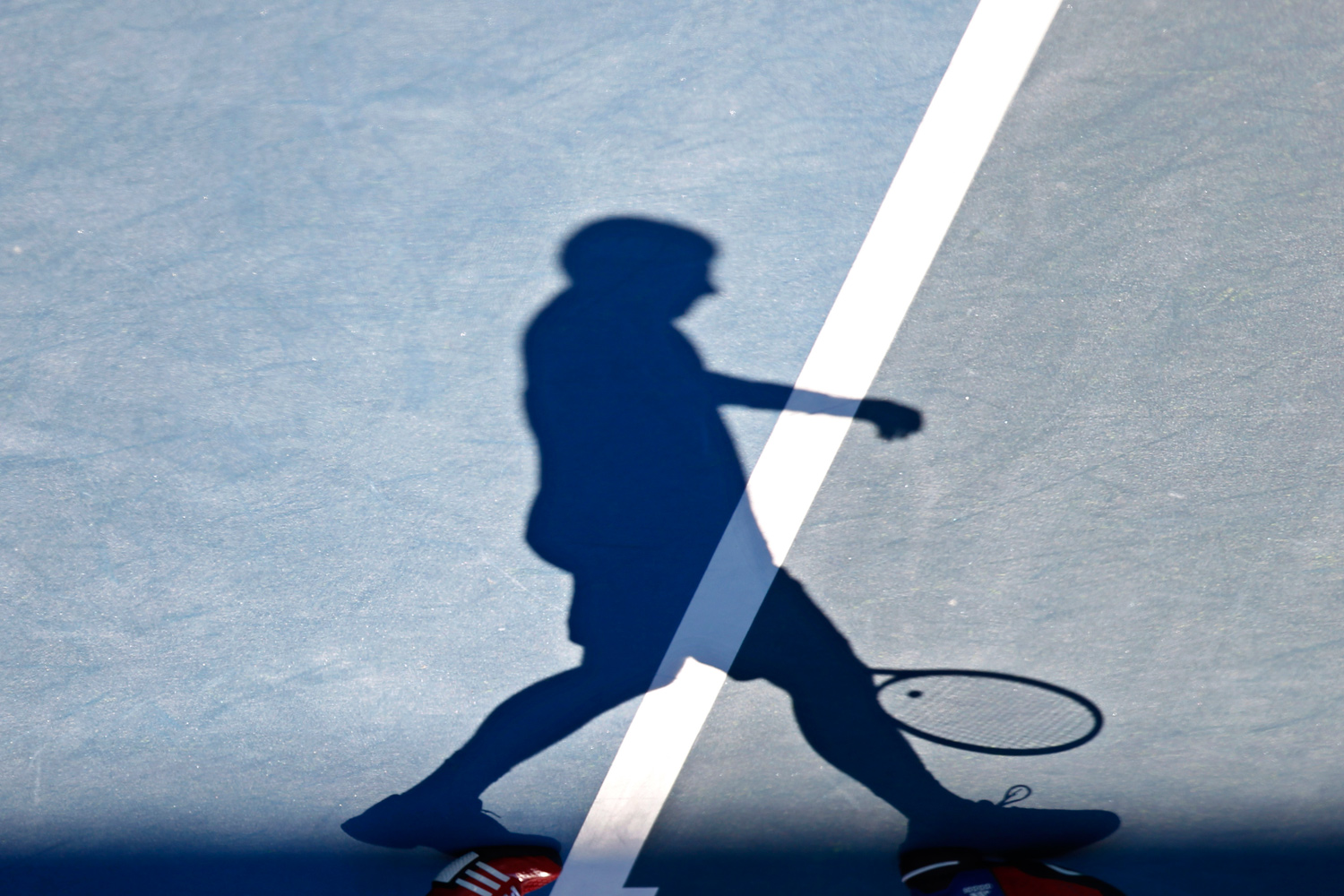 January 14, 2011. Novak Djokovic of Serbia casts his shadow as he walks across the court during a training session at Melbourne Park ahead of the Australian Open tennis tournament.