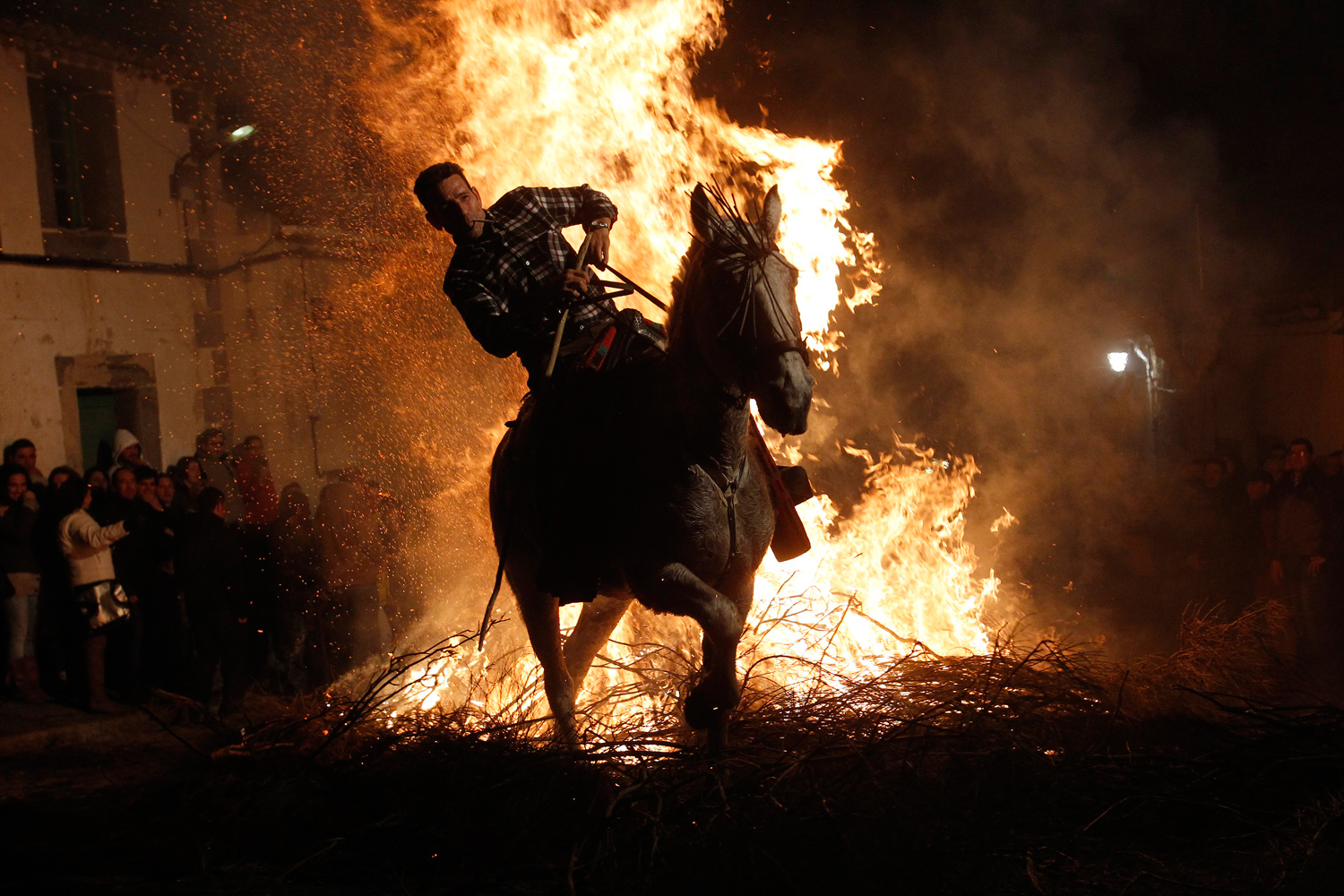 January 16, 2011. A man rides his horse through flames during the  Luminarias  annual religious celebration in the Spanish village of San Bartolome de los Pinares.