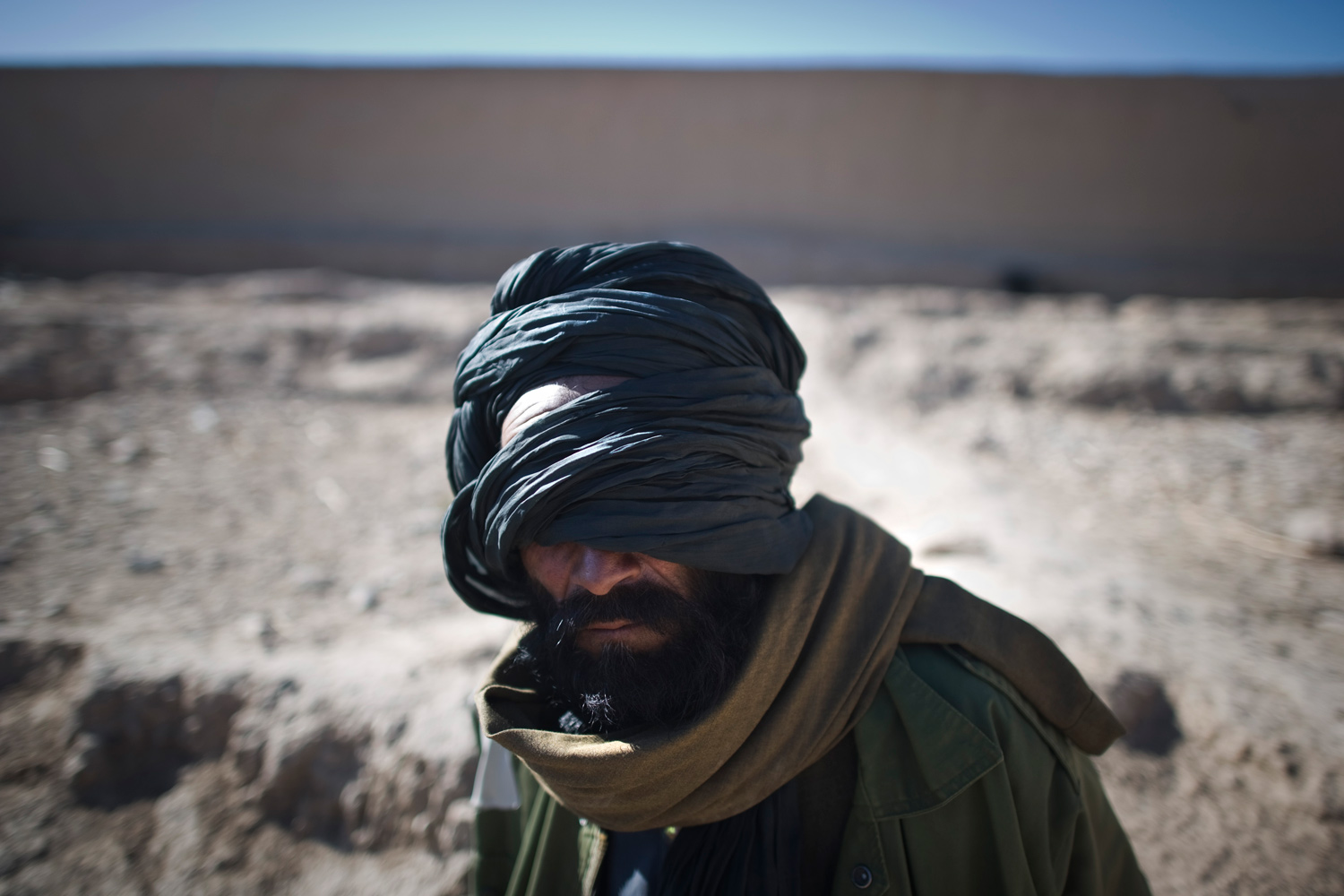 January 23, 2011. An Afghan detainee sits while guarded by U.S. Marines from 1st Battalion 8th, Bravo during an operation in Musa Qala district of Helmand province in Afghanistan.