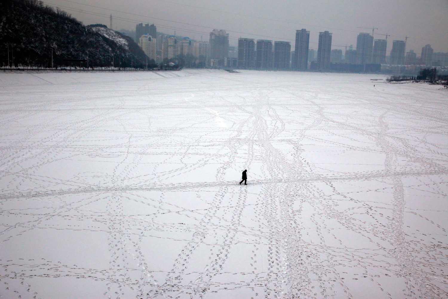January 24, 2011. A man walks across a frozen river in Benxi, northeastern China's Liaoning province.