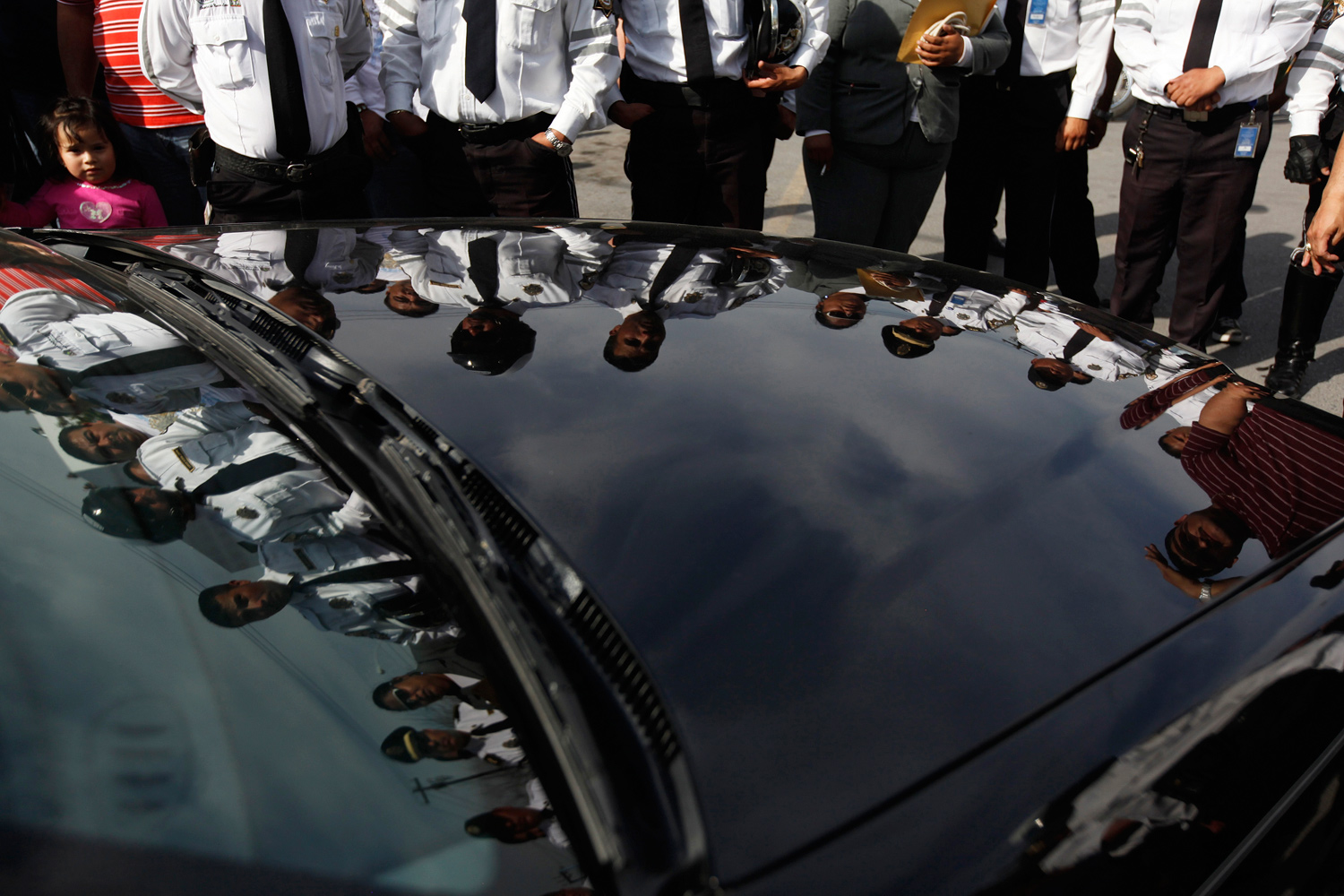 January 31, 2011. Transit officers are reflected on the hearse after a memorial ceremony for their slain colleagues at the police headquarters in Monterrey, Mexico.