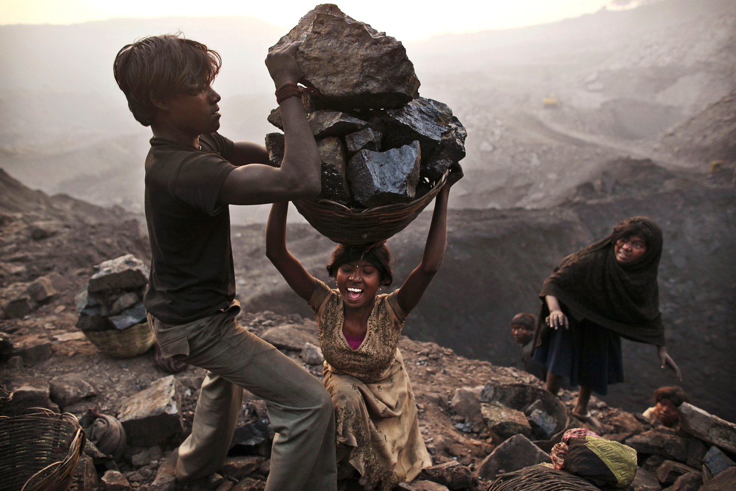 January 6, 2011. A young woman stumbles as she tries to carry a large basket of coal while illegally scavenging at an open-cast mine in Bokapahari, India.
