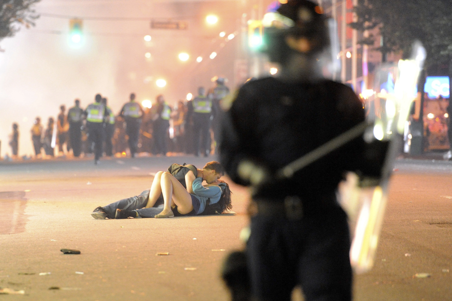 When the Vancouver Canucks lost game 7 of the Stanely Cup finals to the Boston Bruins on their home ice on June 15, local fans took out their frustration in the streets, by rioting, looting and setting fire to cars. During the rampage, Getty photographer Rich Lam captured this image of one couple laying on the ground, seemingly engaged in a romantic moment. The surprising juxtaposition and its metaphorical resonance—make love, not war—made it an internet sensation in the days after it was released.                                                              At first, it was suggested that the photo was a fake, but Lam was able to provide before and after frames that disproved that; but even after the fact, he was not entirely sure what he had witnessed.  It was complete chaos,  he said. Eventually, it became clear that the young woman, later identified as Alexandra Thomas, had been knocked down by the surging                               crowd. Her boyfriend a 29-year-od Australian named Scott Jones had come to her aid. Part of comforting her, the couple explained on a Today show appearance a few days later, was a brief kiss.