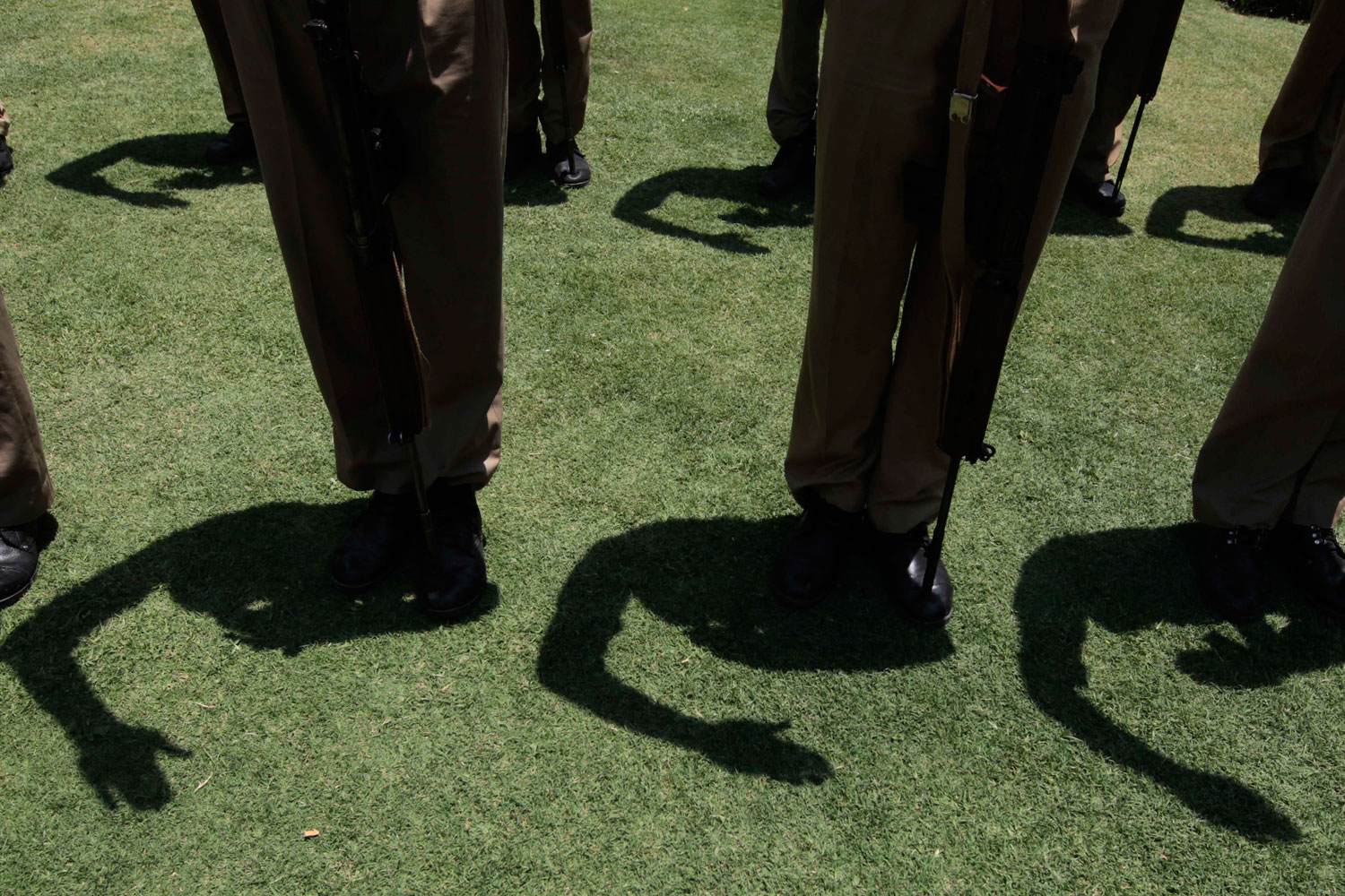 July 6, 2011. Shadows of Indian policeman are cast on ground as they salute during a wreath laying ceremony for their colleague Shabir Ahmed in Srinagar, India.
