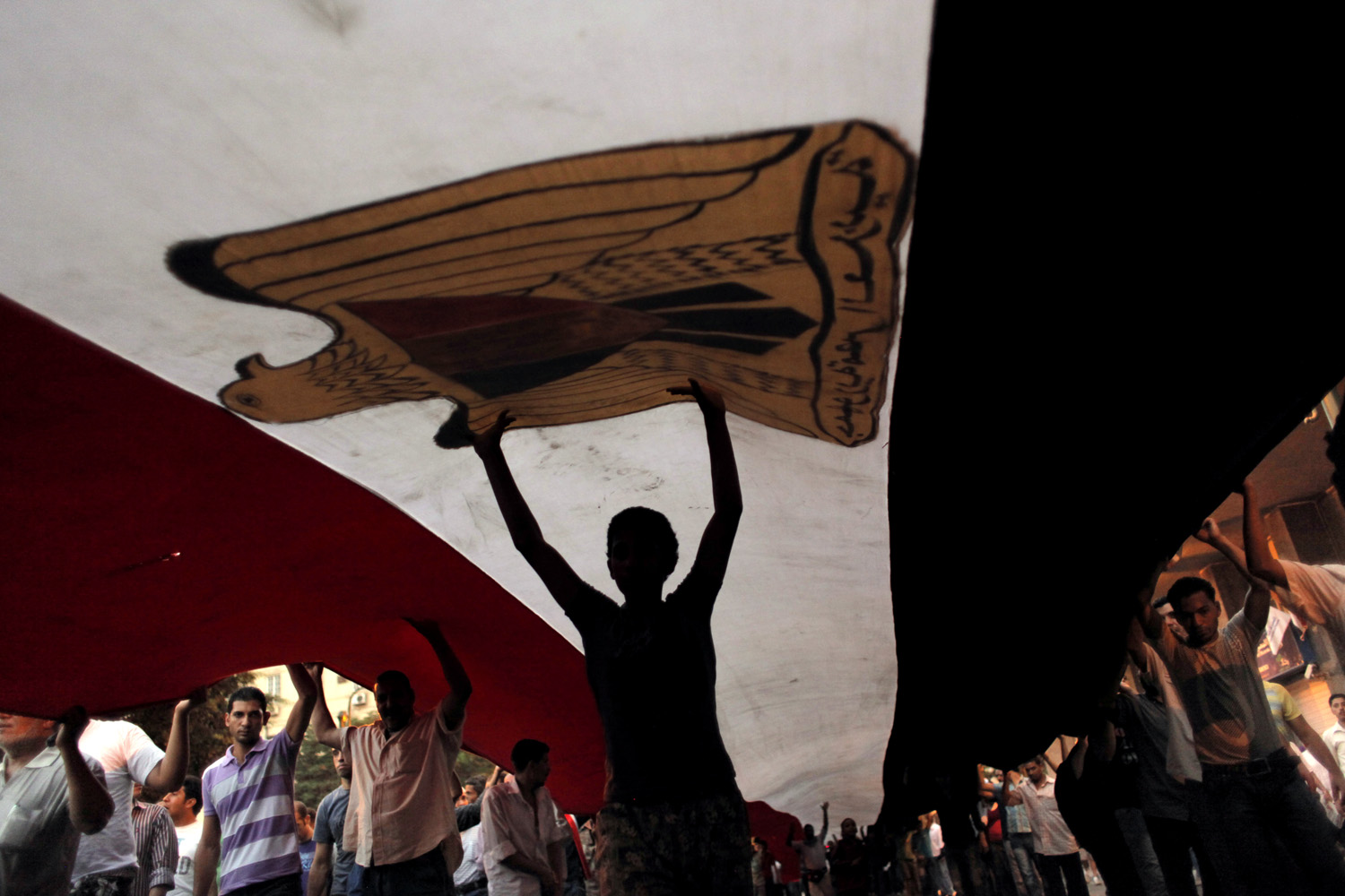July 12, 2011. Protesters march with a giant Egyptian national flag at Tahrir Square in Cairo, Egypt.