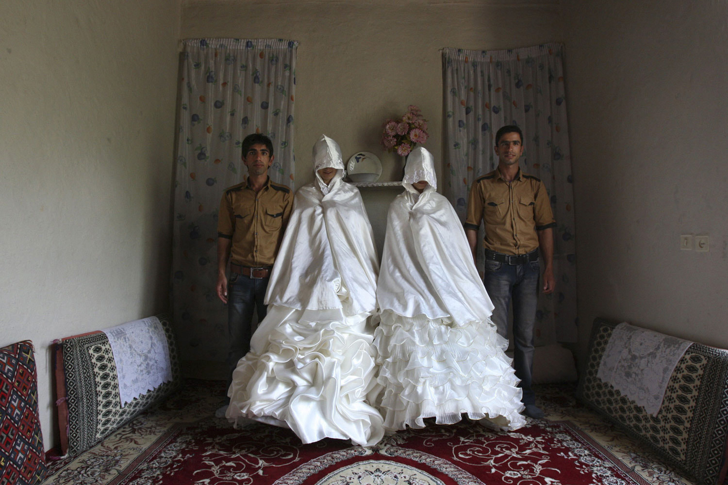 July 15, 2011. Preparing for their dual wedding ceremony, Iranian brothers Javad, left, and Mehdi Jafari pose with their brides-to-be before donning their own formal dress in Ghalehsar.