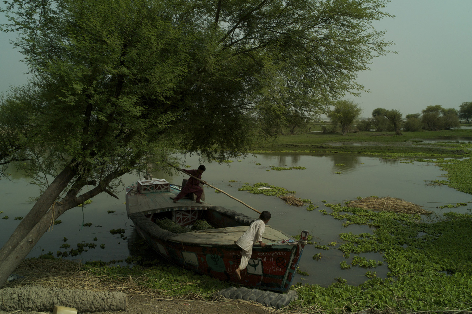 July 21, 2011. Setting out from the embankment below their home in rural Muzaffargarh, brothers Shaista Kawnal and Muhammad Aqib push away from the shore using a bamboo pole as they head out across the flood waters in Pakistan.