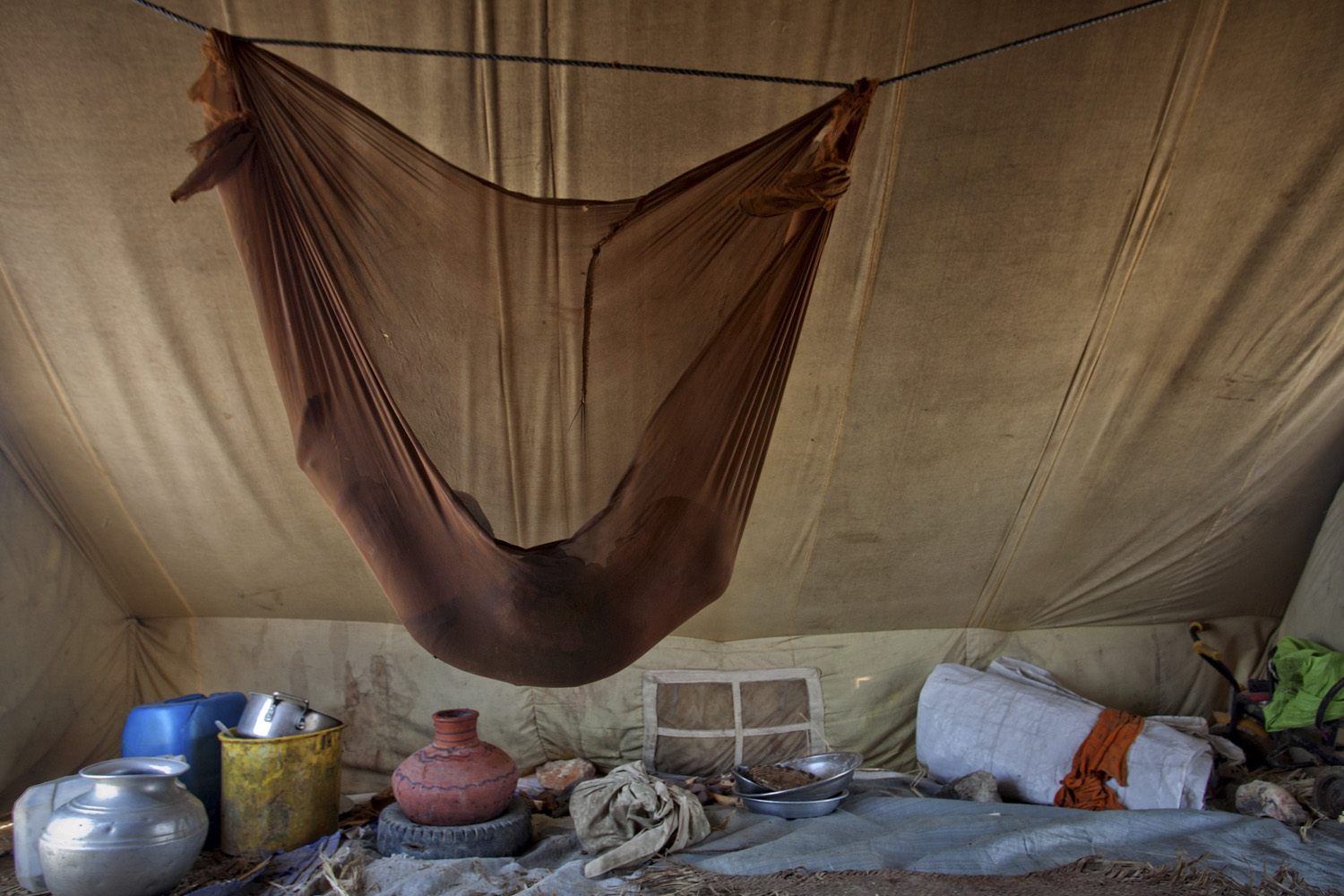July 31, 2011. One and a half-year-old Muskan, internally displaced by the 2010 Pakistan floods, sleeps in a hammock over cooking utensils inside her family's tent set up along a roadside in Jamshoro, in Sindh province.