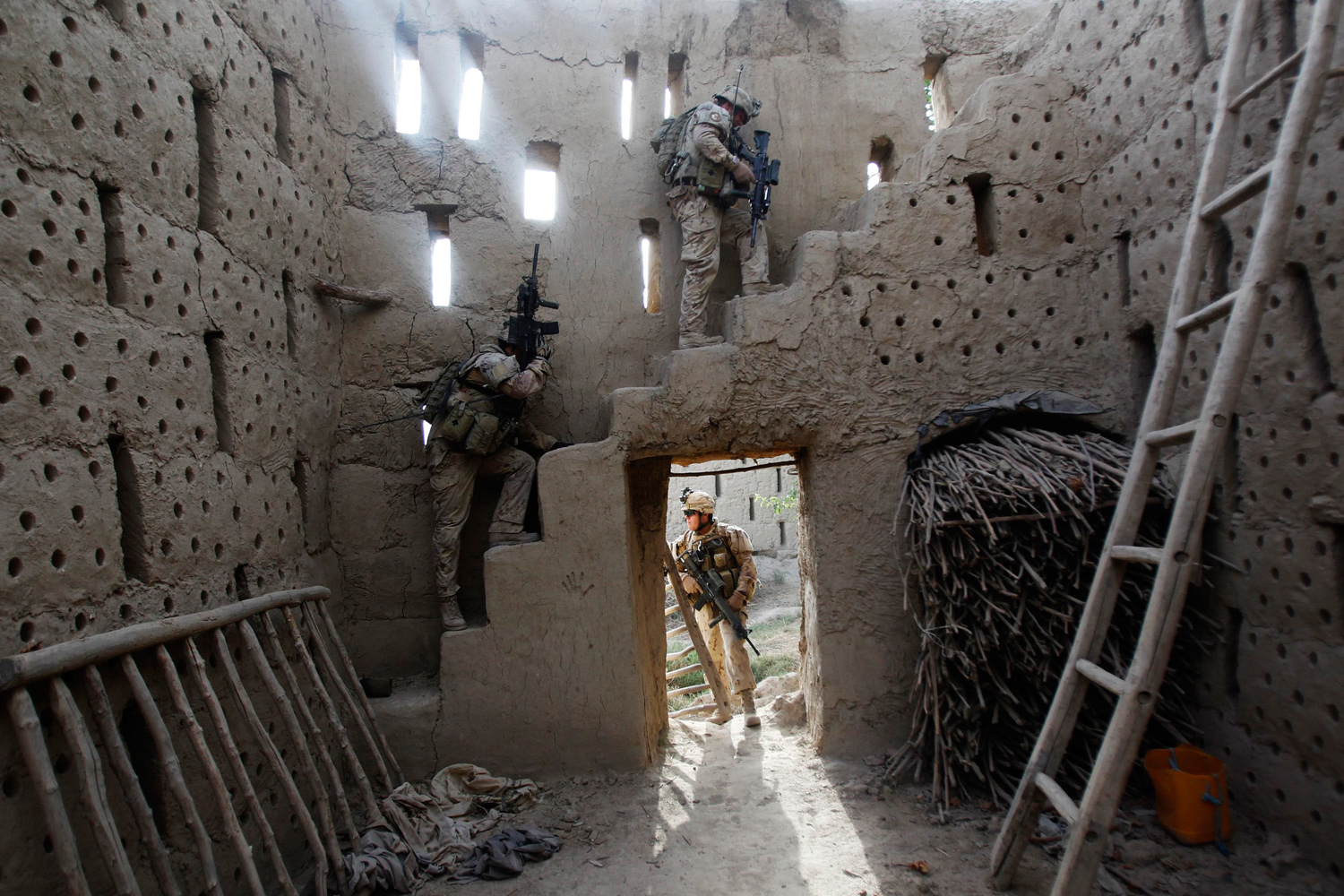 June 13, 2011. Canadian soldiers search inside a barn during a patrol in the Panjwai district of Kandahar, Afghanistan.