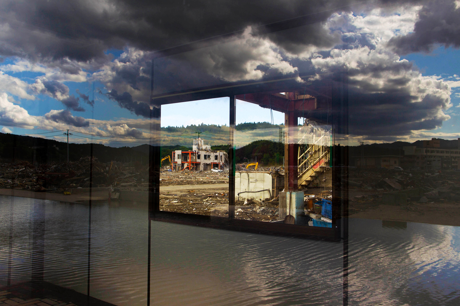 June 14, 2011. The devastated town of Minamisanriku, Japan is reflected in the windows of a newly-constructed fish market shack.