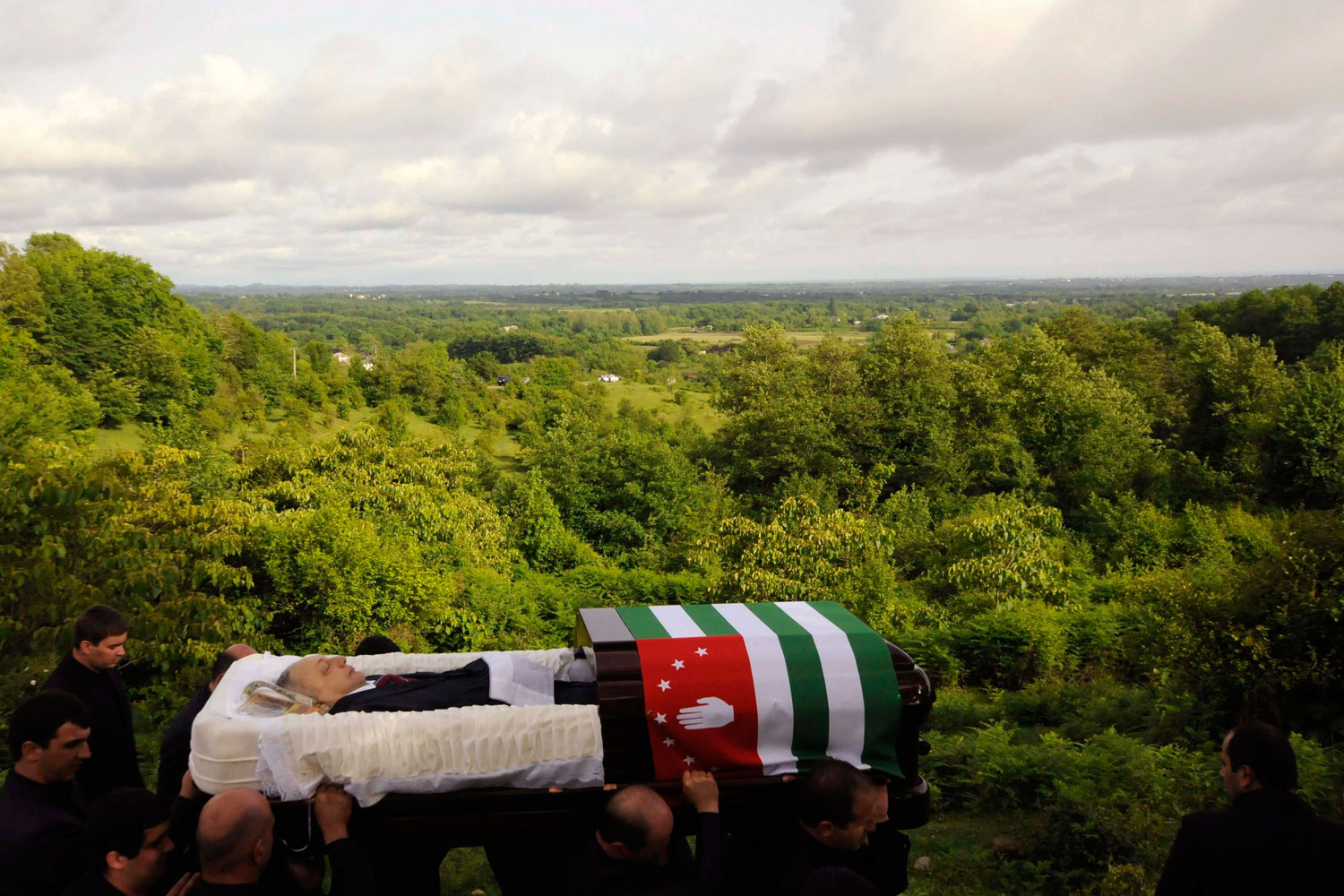June 2, 2011. Pall bearers carry the open coffin of Abkhazia's president Sergei Bagapsh to his funeral in the village of Dzhgiarda.