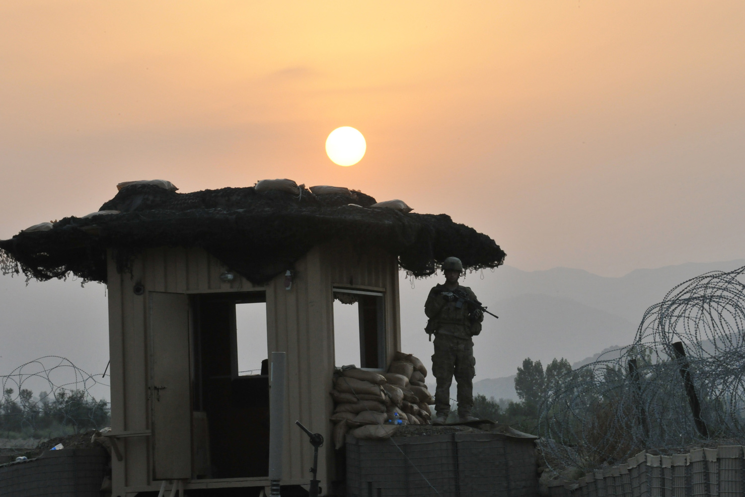June 23, 2011. A U.S. soldier stands on a guard tower as the sun rises at Combat Outpost (COP) Sabari in Khost province in the east of Afghanistan.