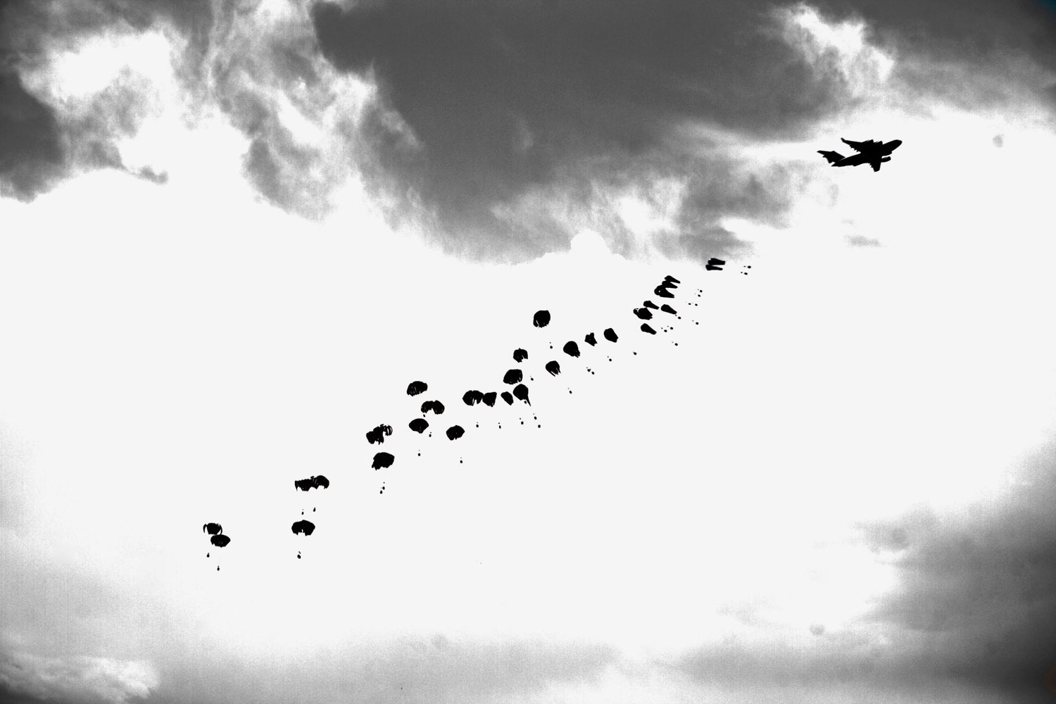 June 4, 2011. Food supplies for U.S. Marines hanging off small parachutes are dropped from a plane as a sandstorm approaches Helmand Province in southern Afghanistan.