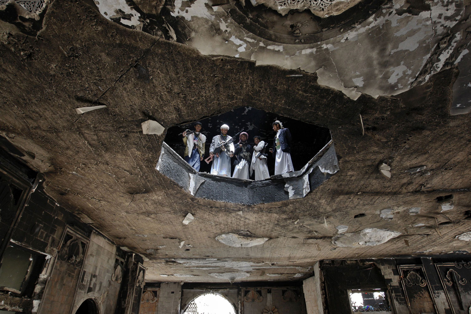 June 7, 2011. Armed supporters of dissident tribal leader Sadiq al-Ahmar inspect damage at his house in Sana'a, Yemen.
