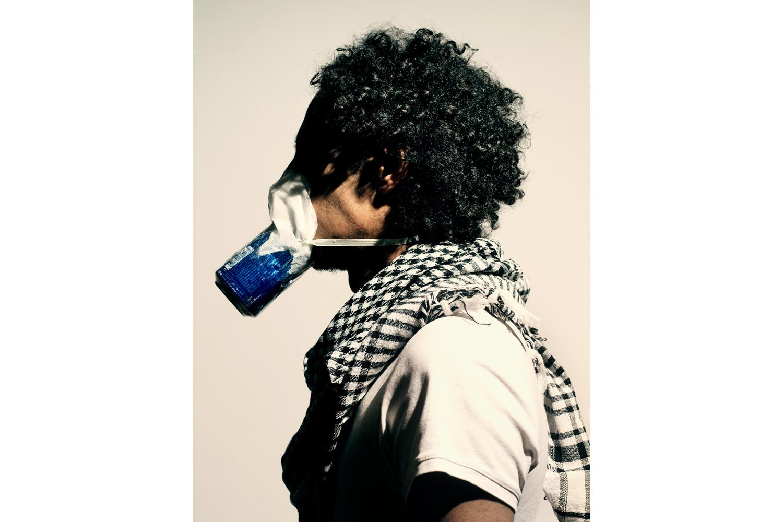 El Teneen, a prominent Egyptian graffiti artist, wears a homemade gas mask.