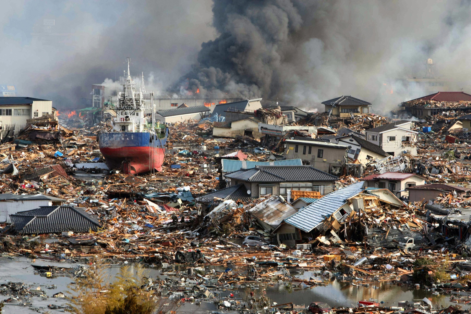March 12, 2011. Amid tsunami flood waters, burning houses and ships are piled in a mass of debris in Kisenuma city, Miyagi prefecture, Japan.