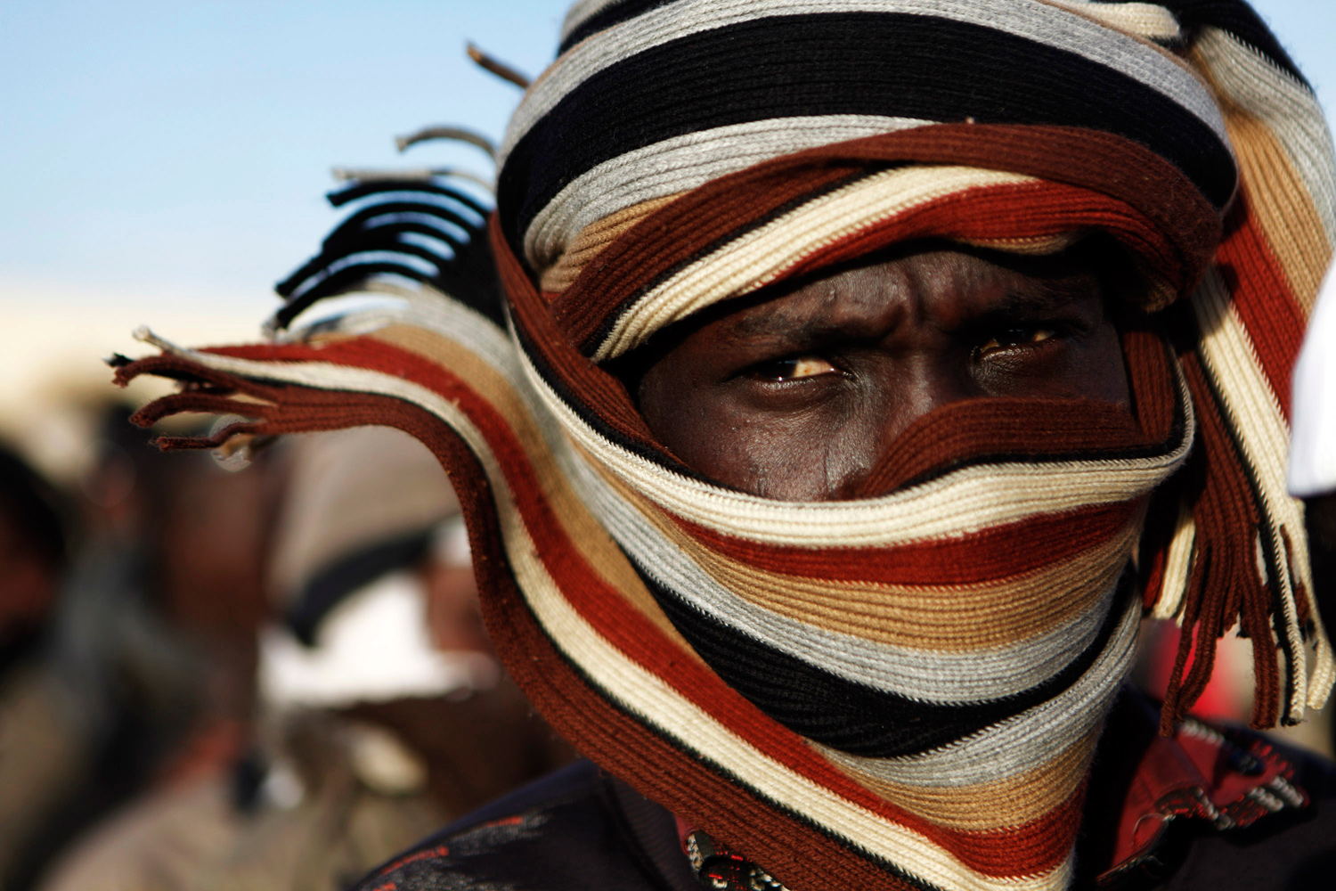 March 16, 2011. A Chadian refugee waits in line for food distribution at the Libya-Egypt border after fleeing fighting in eastern Libya.