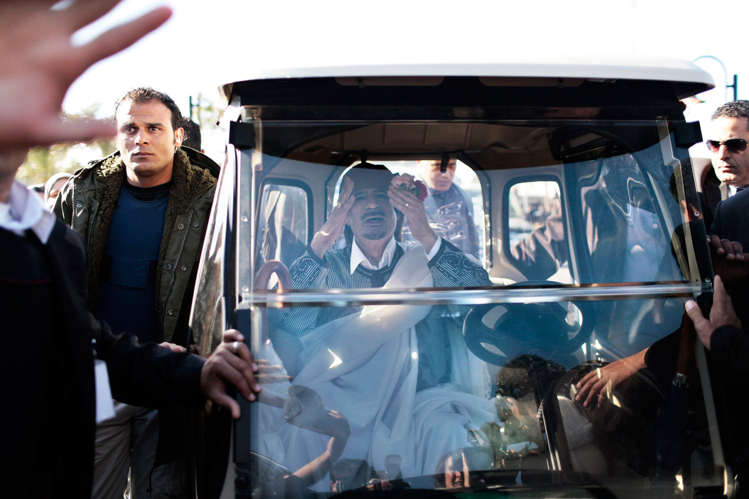 March 2, 2011. Libyan leader Colonel Muammar Gaddafi salutes to journalists from inside a custom-made golf-cart as he leaves the Rixos Al Nasr Tripoli Hotel where he presided over the Libyan People General Congress.