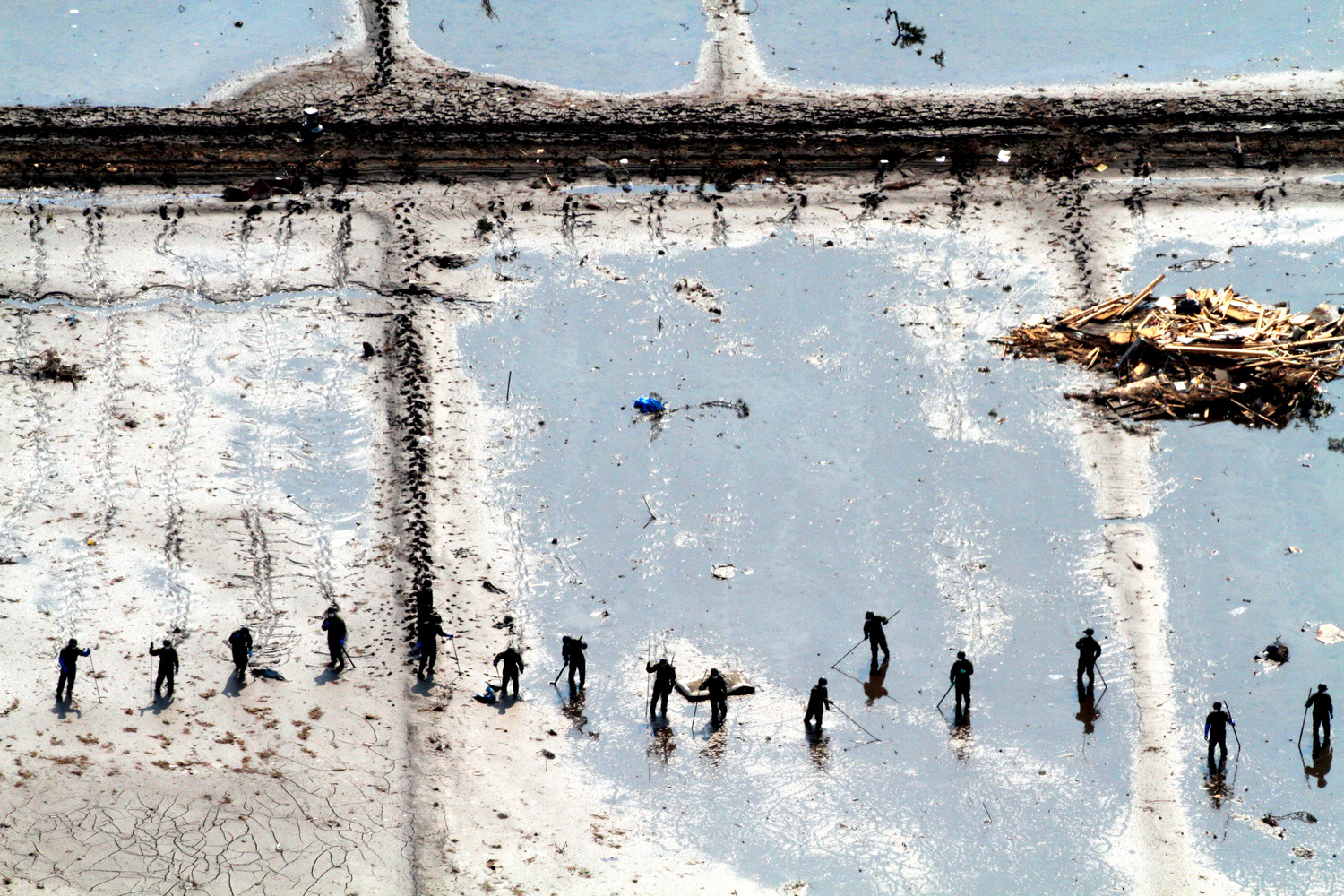 March 25, 2011. In this aerial image, members of Japan Ground Self-Defense Force continue post-tsunami rescue work on a muddy field in Shichigahama, Miyagi, Japan.