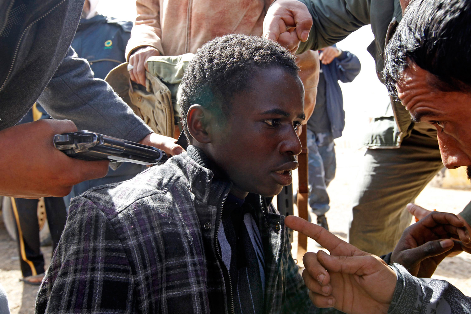 March 3, 2011. Rebels hold a young man, whom they accused of being a Gaddafi loyalist, at gunpoint between the towns of Brega and Ras Lanuf.