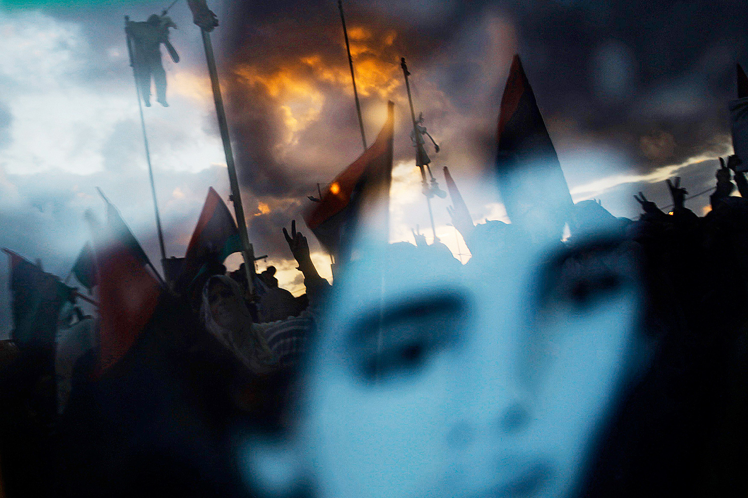 March 6, 2011. Anti-Gaddafi protesters hanging effigies of Libyan leader Muammar Gaddafi are reflected in a photo of a youth who was killed in clashes in Benghazi.