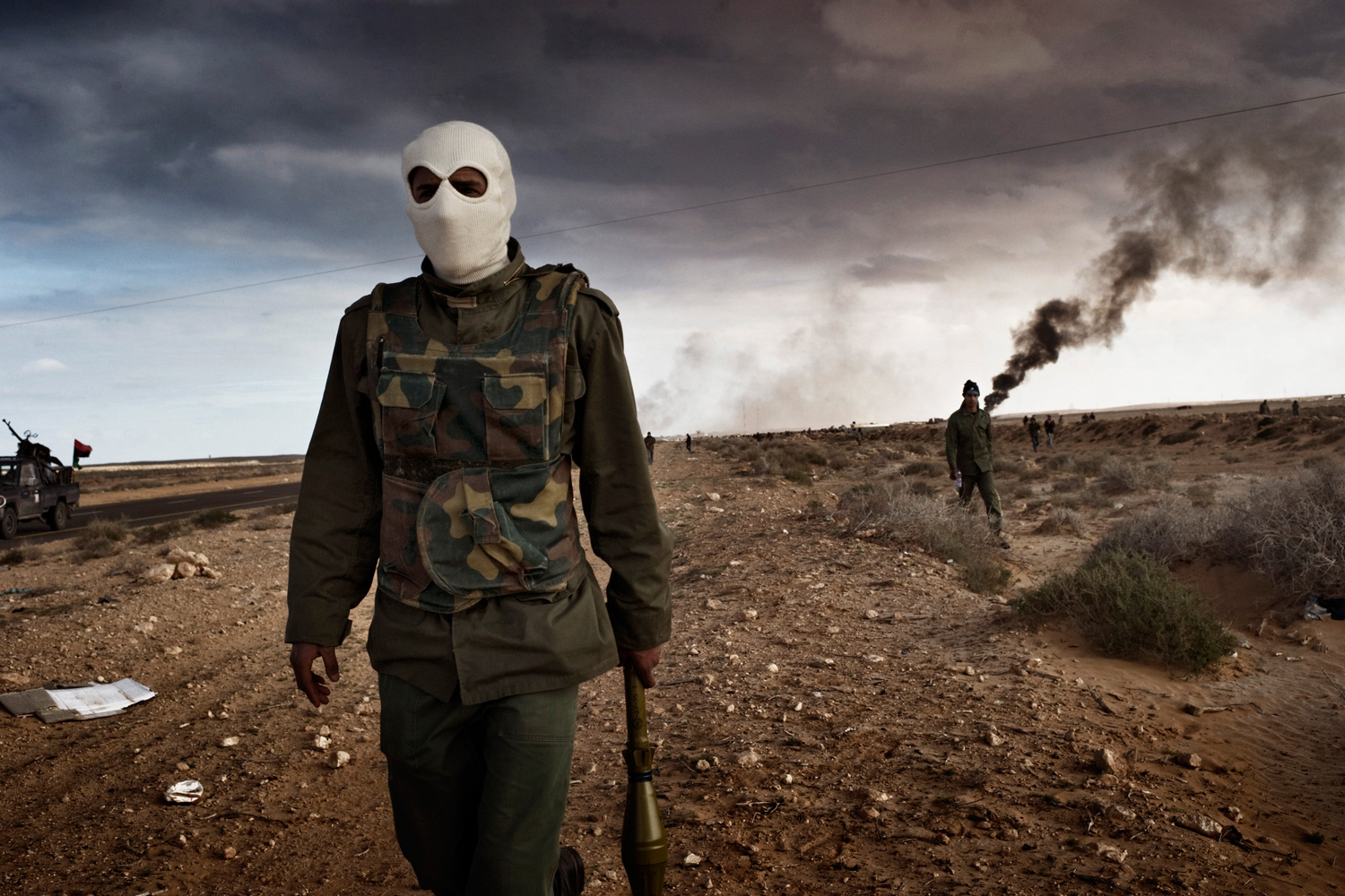 March 9, 2011. Libyan rebels advance during a battle with government troops as an oil facility burns.