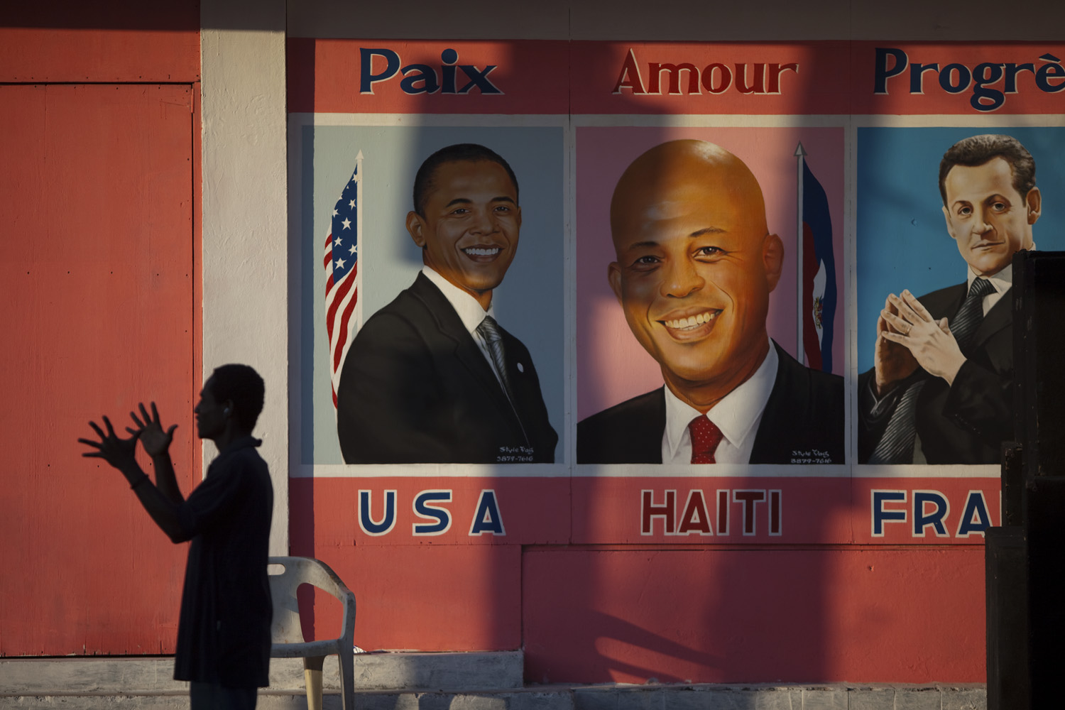 May 14, 2011. A man claps his hands in front of a new painting depicting three presidents on inauguration day for newly-elected Haitian President Michel Martelly in the Petionville neighborhood of Port-au-Prince, Haiti.