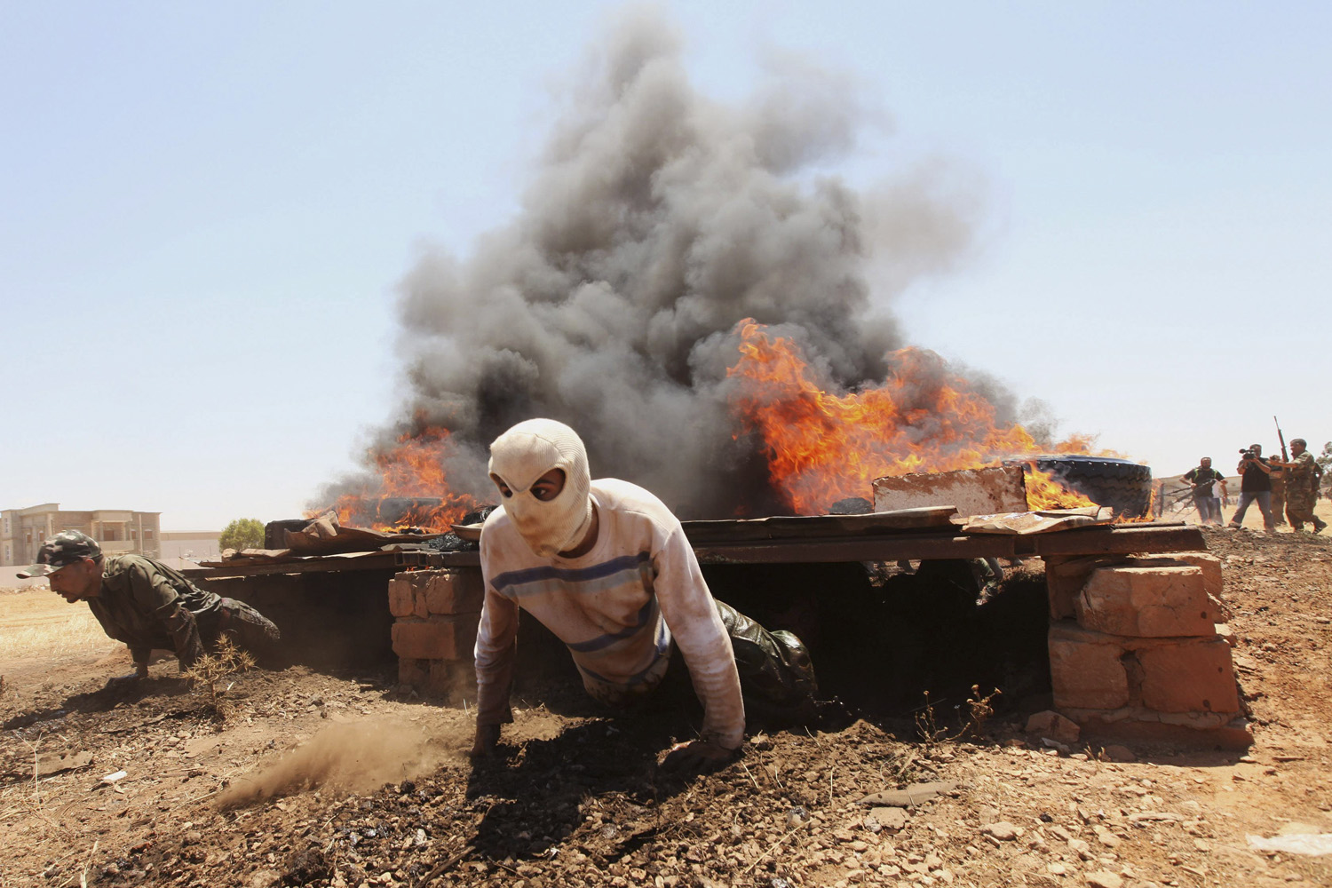 May 15, 2011. Civilian volunteers of the rebel army clear an obstacle course during training in Benghazi, Libya.