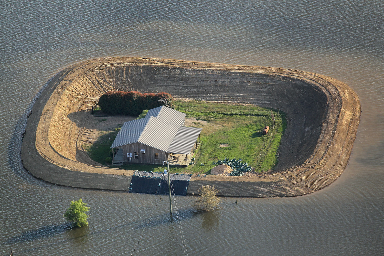 May 18, 2011. A levee protects a home surrounded by floodwater from the Yazoo River near Vicksburg, Mississippi. Heavy rains left the ground saturated and caused widespread flooding along the Mississippi River from Illinois to Louisiana.