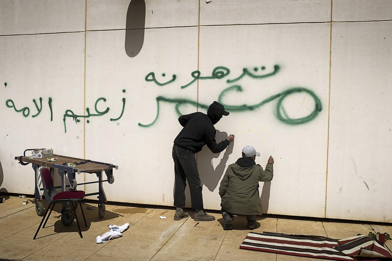 March 27, 2011. Libyan rebels scrawl graffiti on a wall near a hospital in Ras Lanuf. The wall was previously decaded, in green, by Gaddafi troops.