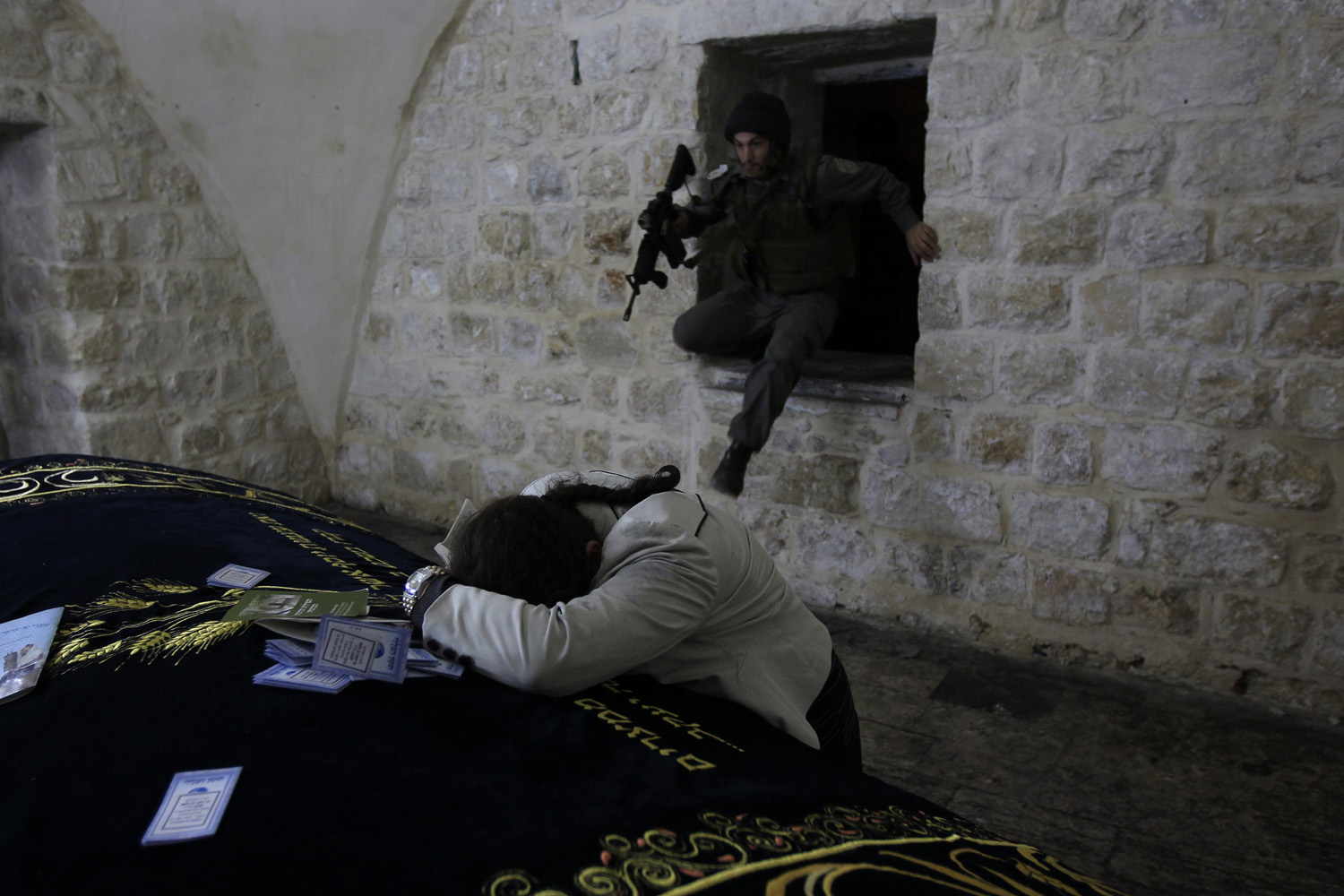 May 30, 2011. Israeli border policeman enters through a window as a Jewish worshiper prays in Joseph's Tomb in the West Bank city of Nablus.