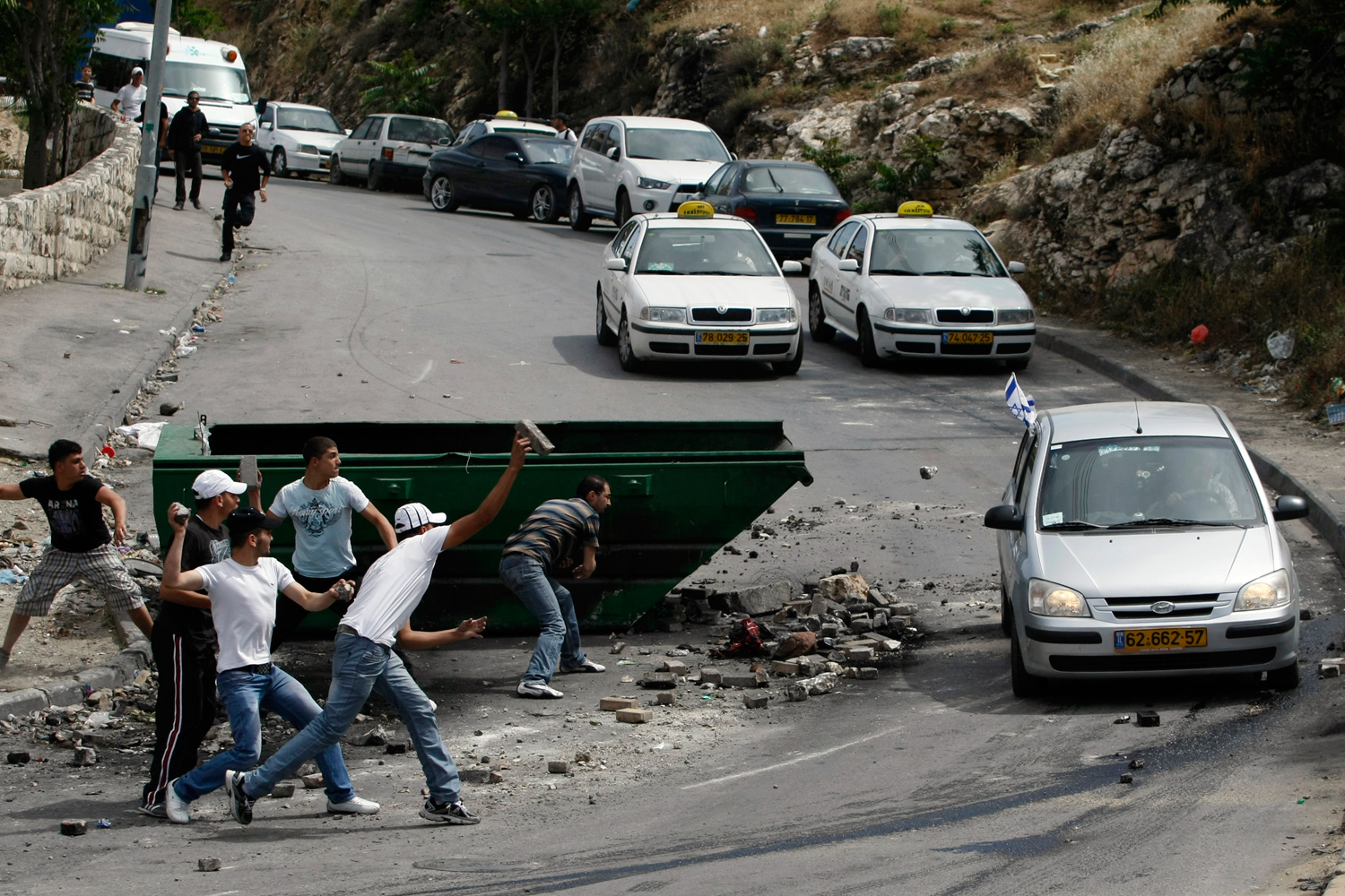 May 6, 2011. Palestinian youths throw bricks and stones at an Israeli car that mistakenly drove into the mostly Arab neighborhood of Silwan in East Jerusalem.
