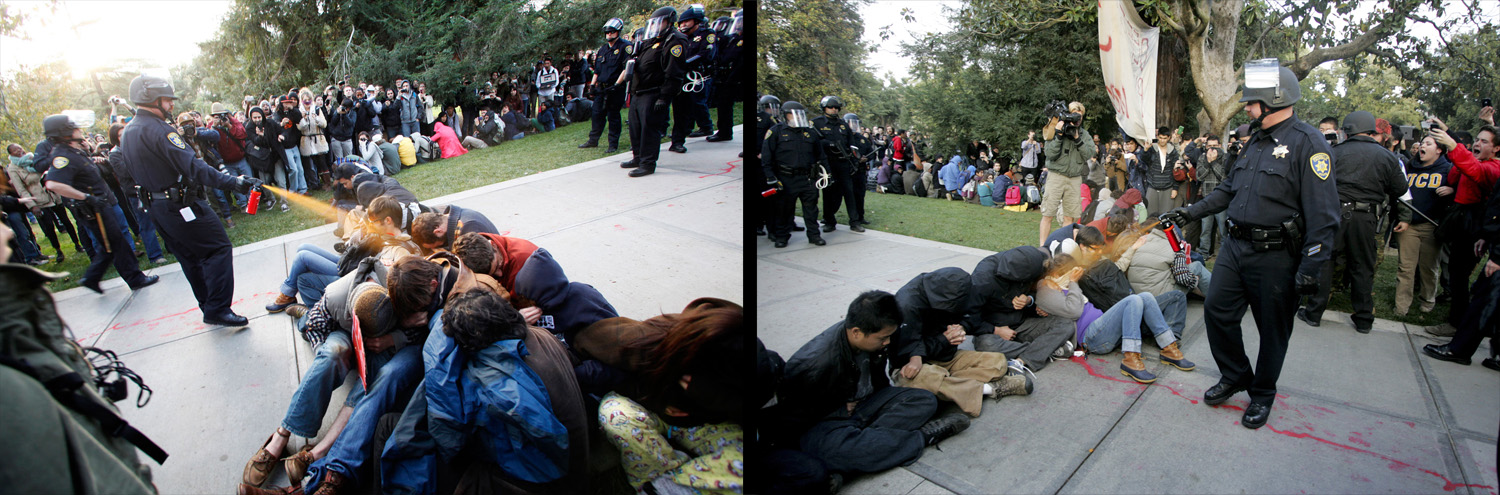 November 18, 2011. University of California, Davis Police Lt. John Pike uses pepper spray to move Occupy UC Davis protesters while blocking their exit from the school's quad in Davis, California. Two University of California, Davis police officers involved in pepper spraying seated protesters were placed on administrative leave on November 20, 2011, as the chancellor of the school accelerated the investigation into the incident.