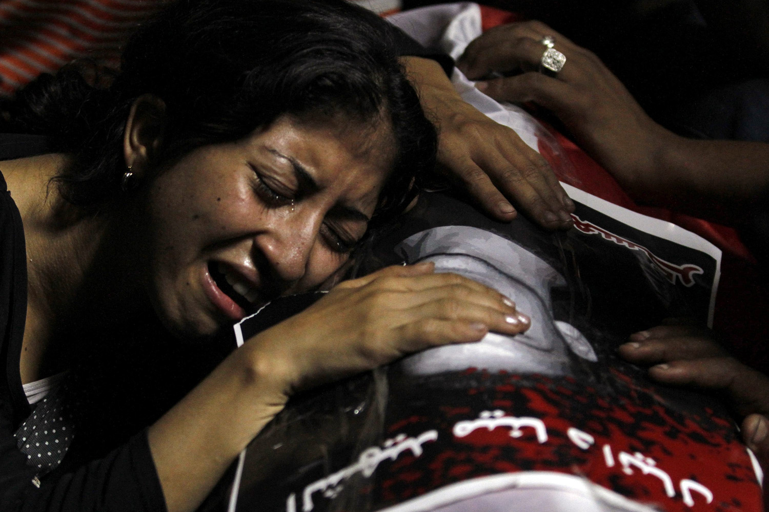 October 10, 2011. An Egyptian Christian woman mourns on the coffin of Coptic Christian Mina Daniel, who was killed during clashes with soldiers and riot police, at the morgue of the Coptic Hospital in Cairo.